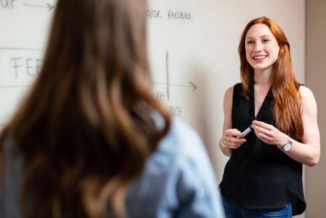 Female teacher standing infront of a student