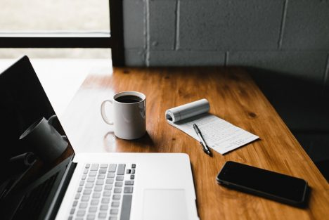 Laptop, coffee, notepad and mobile phone on a desk